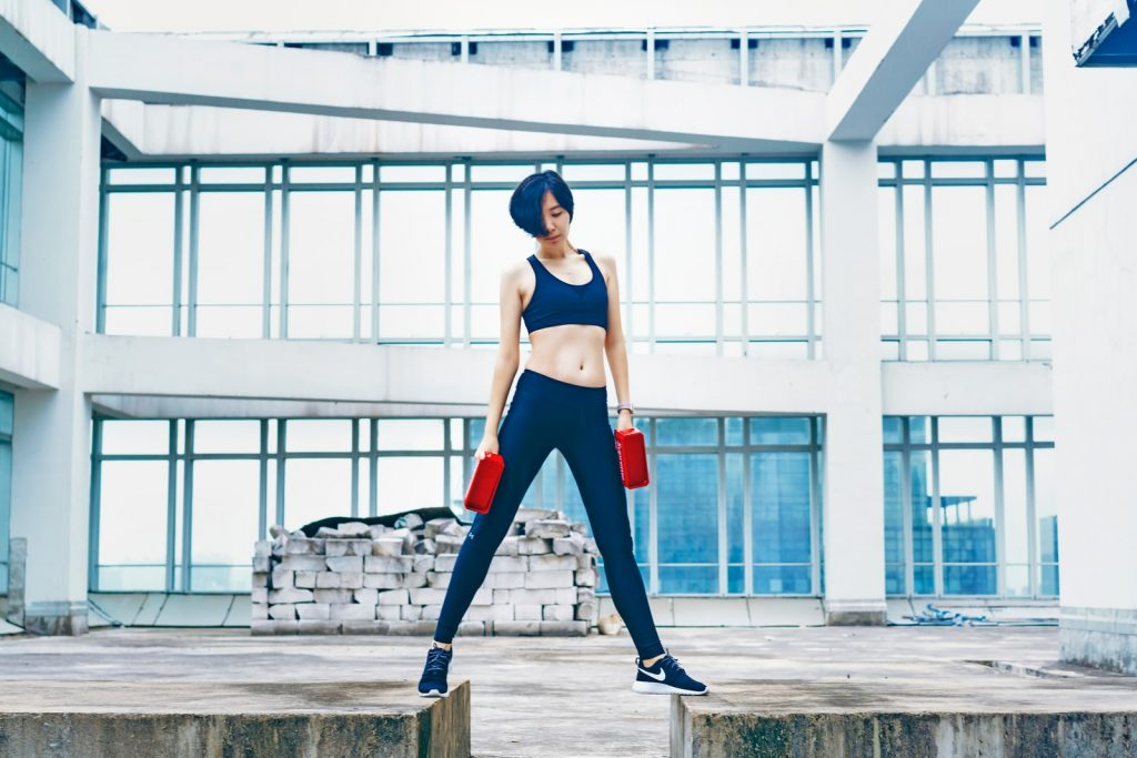 woman wearing black sports bra and pants while holding two red weights